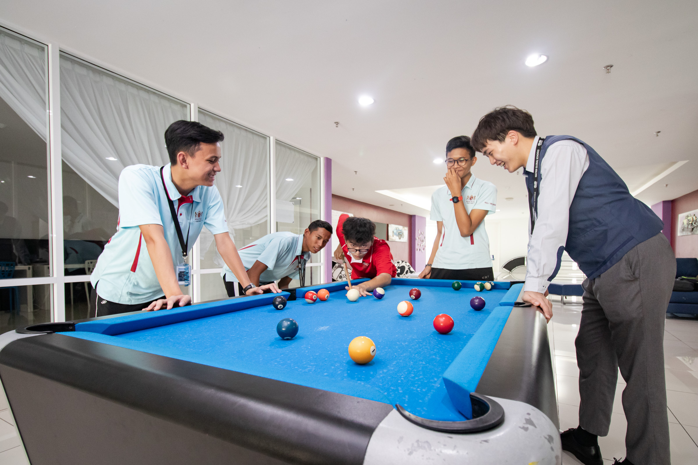 a group of students playing pool at snooker gameroom