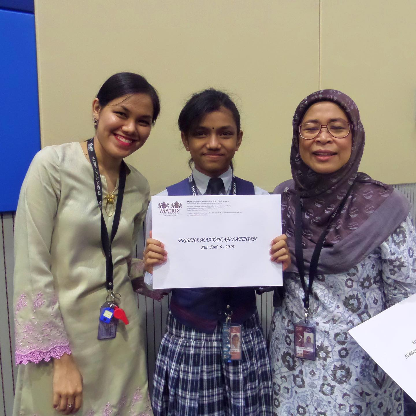 students holding the certificate taking photo with teachers